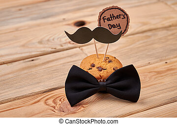 Muffin with mustache on wood.