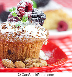muffin with whipped cream, cake with icing, raspberry, blackberry and mint on a plate on plaid fabric