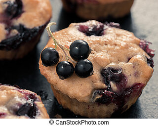 Muffins with black currant on dark background close up. Selective focus