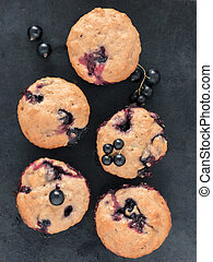 Muffins with black currant on dark background close up. Top view or flat lay