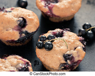 Muffins with black currant on dark background close up