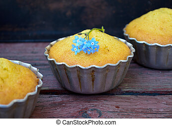 Muffins with blue flowers on wooden background