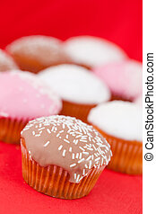 Muffins with icing sugar on a red tablecloth