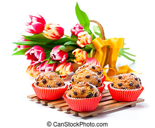 Muffins with tulips isolated on white background