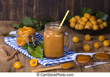 Mug glass of juice smoothie shake from yellow plum, jam and ripe yellow plum, on a vintage wooden table. Bio healthy food and drink. Organic diet