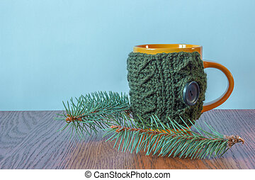 mug in knitted cover standing next to a Christmas tree branche
