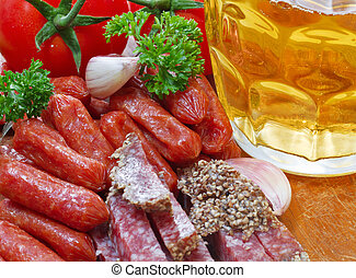 mug of beer and an assortment of salami and vegetables on a cutting board