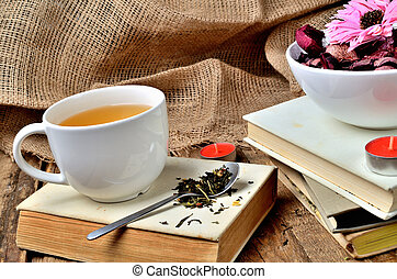 Mug of black tea and spoon with tea loose on an old, vintage shabby book, candle and dried flowers in background