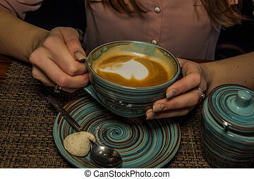 Mug of coffee on a wooden table with sugarbowl , the girl holds in her hand one cup of milk coffee in an air. A photo indicates a relaxing coffeebreak