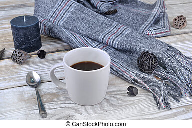 mug of coffee with scarf and candle on a table