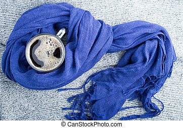 Mug of coffee wrapped in blue cotton scarf