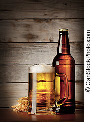 Mug of lager beer with a bottle on a wooden background