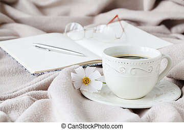 mug of morning coffee in bed, reading a book, spring flower