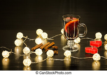 Mug of mulled wine with spices, candles in the shape of a heart and lanterns. Black background