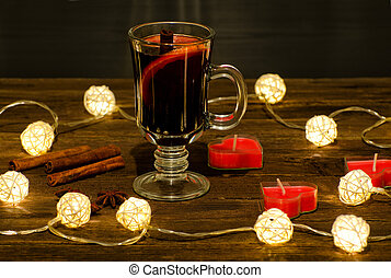 Mug of mulled wine with spices, candles in the shape of a heart on a wooden table, a garland of lanterns. Cinnamon sticks, anise