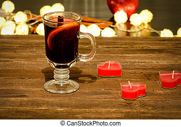 Mug of mulled wine with spices, candles in the shape of a heart on a wooden table. Garland of lanterns in the background