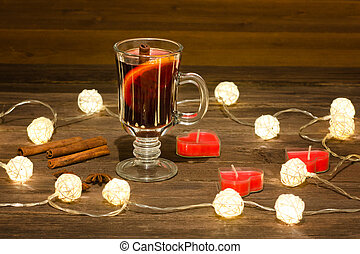 Mug of mulled wine with spices, candles in the shape of a heart on a wooden table