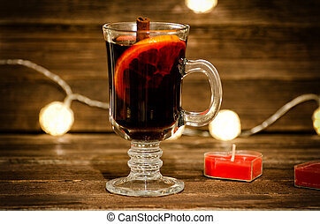 Mug of mulled wine with spices close up. Candle in the shape of a heart on a wooden table, lanterns in the background