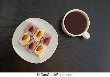 Mug of tea and Turkish Delight with almonds on a plate, top view, black background