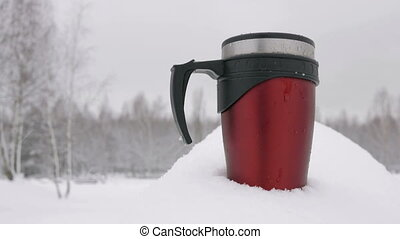 Mug standing in a snowy forest in the heavy snowfall. Dark red in color with black handle