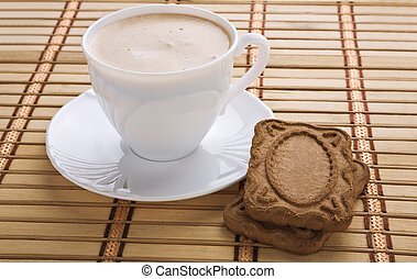 mug with capuchino and cookie on a mat