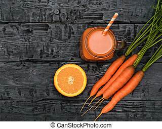 Mug with carrot smoothie, ginger root and orange on wooden rustic dark table. The view from the top. Flat lay.
