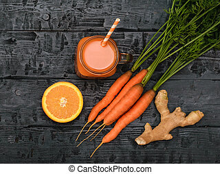 Mug with carrot smoothie, ginger root and orange on wooden table. The view from the top. Flat lay.