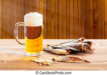Mug with frothy beer and dried fish on wooden background