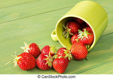 Mug with strawberries on a green background