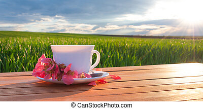 Mug with tea on the table in the green field
