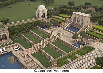 Terraced gardens and swimming pool in a Mughal style walled garden. Luxury Hotel, Agra, India
