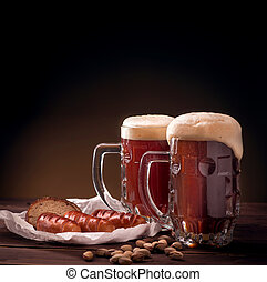 Mugs of beer with snacks on wooden table