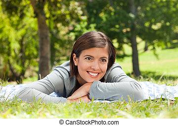 mujer, acostado, en el parque
