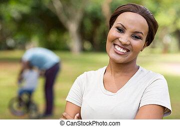 mujer africana, posición, delante de, familia , aire libre