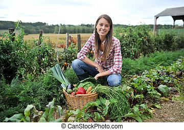 mujer, arrodillado, en, jardín vegetal