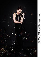 mujer asiática, con, moda, maquillaje, en, lujo, vestido negro, mientras, confeti, caer, en, ella.