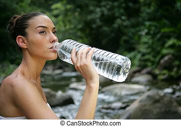 mujer beber de botella de agua