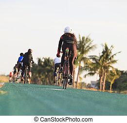 mujer, bicicleta que cabalga, en, verde, pista, con, hermoso, jinete, traje