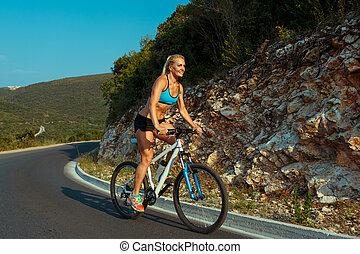 mujer, cabalgar bicicleta, en, un, camino de la montaña