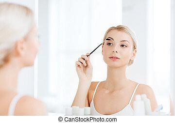 mujer, cepillado, ceja, con, cepillo, en, cuarto de baño
