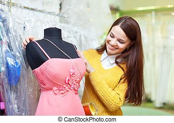 mujer, chooses, vestido de la tarde
