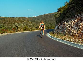 mujer, ciclista, cabalgar bicicleta, en, un, camino de la montaña