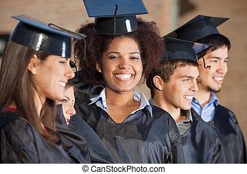 mujer, con, amigos, en, día de graduación, en, colegio