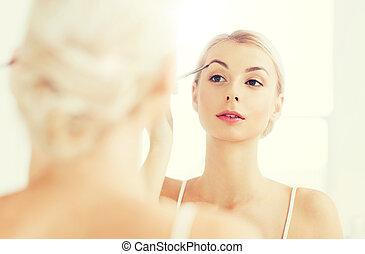 mujer, con, cepillo, hacer, ceja, maquillaje, en, cuarto de baño