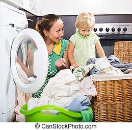 mujer con el niño, cerca, lavadora