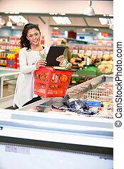 mujer, con, electrónico, lista de compras