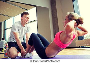 mujer, con, entrenador personal, hacer, sit ups, en, gimnasio