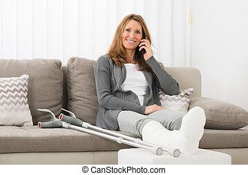 mujer, con, enyesado, pierna, hablar celular