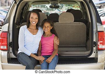 mujer, con, niña joven, sentado, detrás de, furgoneta, sonriente