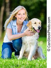 mujer, con, perro, el sentarse en la hierba